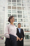 Young business women standing outside of CBD, portrait Royalty Free Stock Photos