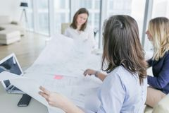 Young business women working on business drawings. Young business women working on drawings, papers at the table in modern office. Shallow DOF stock images