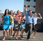 Young business workers run down steet. Royalty Free Stock Images
