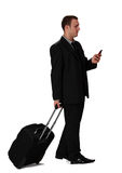 Young businessman. With a suitcase reading a phone message against a white background Royalty Free Stock Images