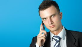 Young businessman. Attractive young businessman in black suit with mobile phone Stock Photography