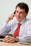 Young businessman. The young smiling businessman speaks by phone Royalty Free Stock Photo