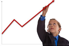Young businessman. Boy dressed as businessman points at the diagram Royalty Free Stock Photography