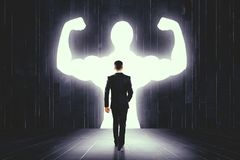 Confidence and development concept. Young businessman with abstract strong muscly projection on wall in interior. Confidence and development concept royalty free stock photography