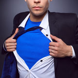 Young businessman acting like a super hero and tearing his shirt,  on gray background.  Stock Photo