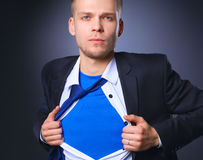 Young businessman acting like a super hero and tearing his shirt, isolated on gray background.  Royalty Free Stock Images