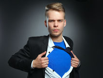 Young businessman acting like a super hero and tearing his shirt, isolated on gray background.  Stock Photo