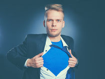 Young businessman acting like a super hero and tearing his shirt, isolated on gray background.  Stock Image