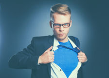 Young businessman acting like a super hero and tearing his shirt, isolated on gray background.  Stock Photos