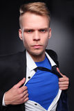 Young businessman acting like a super hero and tearing his shirt, isolated on gray background.  Royalty Free Stock Photo