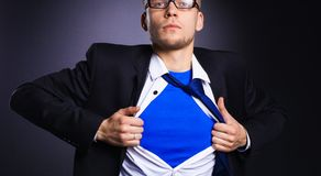 Young businessman acting like a super hero and tearing his shirt, isolated on gray background.  Royalty Free Stock Photos