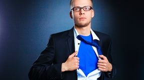 Young businessman acting like a super hero and tearing his shirt, isolated on gray background.  Stock Photography