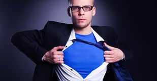 Young businessman acting like a super hero and tearing his shirt,  on gray background. Young businessman acting like a super hero and tearing his shirt Royalty Free Stock Photo
