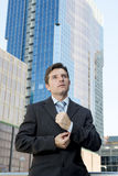 Young businessman adjusting shirt cuff link  outdoors at exterior office building Royalty Free Stock Photo
