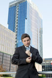 Young businessman adjusting shirt cuff link  outdoors at exterior office building Stock Photography