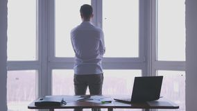 Young businessman admire view from the window spreads his hands in an office.3840x2160 stock footage
