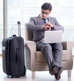 Young businessman in airport business lounge waiting for flight stock photography
