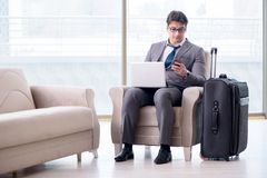 The young businessman in airport business lounge waiting for flight. Young businessman in airport business lounge waiting for flight Royalty Free Stock Photo