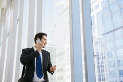Young businessman in airport. Casual urban professional business man using smartphone smiling happy inside office building. Man on smart phone - young Stock Photos