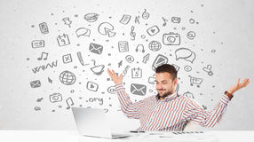 Young businessman with all kind of hand-drawn media icons in bac Royalty Free Stock Images
