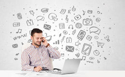 Young businessman with all kind of hand-drawn media icons in bac Royalty Free Stock Photo
