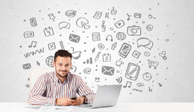 Young businessman with all kind of hand-drawn media icons in bac Stock Photo