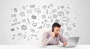 Young businessman with all kind of hand-drawn media icons in bac Royalty Free Stock Image