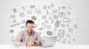 Young businessman with all kind of hand-drawn media icons in bac Stock Photography
