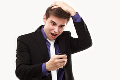 Young businessman amazedly looking at the phone Stock Photography