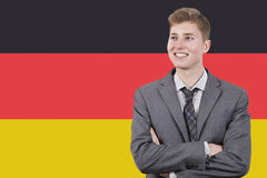 Young businessman with arms crossed over German flag Stock Photography