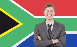 Young businessman with arms crossed over South African flag Royalty Free Stock Image
