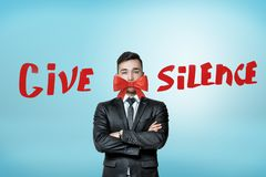 A young businessman, arms folded, with a beautiful red bow covering his mouth and the title `Give Silence`. royalty free stock image
