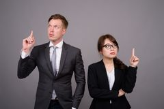 Young businessman and young Asian businesswoman against gray bac. Studio shot of young handsome businessman and young beautiful Asian businesswoman wearing royalty free stock photography