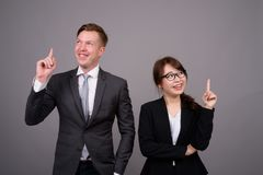 Young businessman and young Asian businesswoman against gray bac. Studio shot of young handsome businessman and young beautiful Asian businesswoman wearing stock photography