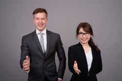 Young businessman and young Asian businesswoman against gray bac. Studio shot of young handsome businessman and young beautiful Asian businesswoman wearing stock image