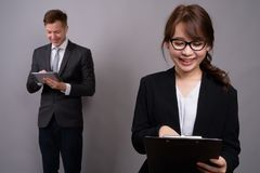 Young businessman and young Asian businesswoman against gray bac. Studio shot of young handsome businessman and young beautiful Asian businesswoman wearing stock photos