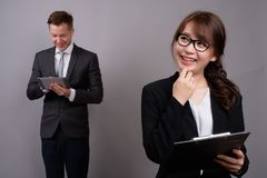 Young businessman and young Asian businesswoman against gray bac. Studio shot of young handsome businessman and young beautiful Asian businesswoman wearing royalty free stock image