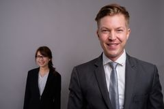 Young businessman and young Asian businesswoman against gray bac. Studio shot of young handsome businessman and young beautiful Asian businesswoman wearing royalty free stock photos