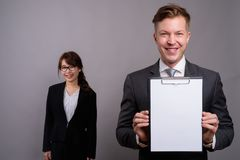 Young businessman and young Asian businesswoman against gray bac. Studio shot of young handsome businessman and young beautiful Asian businesswoman wearing stock photo
