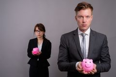 Young businessman and young Asian businesswoman against gray bac. Studio shot of young handsome businessman and young beautiful Asian businesswoman wearing stock images