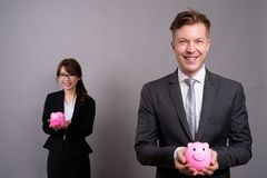 Young businessman and young Asian businesswoman against gray bac. Studio shot of young handsome businessman and young beautiful Asian businesswoman wearing royalty free stock images