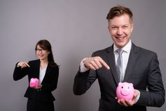 Young businessman and young Asian businesswoman against gray bac. Studio shot of young handsome businessman and young beautiful Asian businesswoman wearing royalty free stock photo