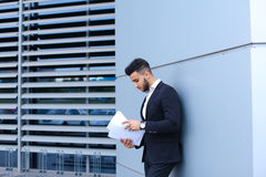 Young businessman asian guy holds and considers, reads and sorts Stock Photos