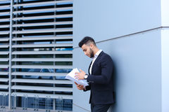 Young businessman asian guy holds and considers, reads and sorts Royalty Free Stock Photos