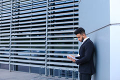 Young businessman asian guy holds and considers, reads and sorts Royalty Free Stock Images