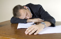 Young Businessman Asleep At His Desk In Office Stock Photo
