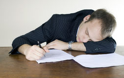 Young businessman asleep at his desktop. Young businessman, asleep on his office table, with a contract left to sign in front of him Royalty Free Stock Photography