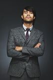 Young businessman with attitude. Portrait of young business person looking at you with an attitude. Businessman with arms crossed on black background. Mixed race royalty free stock photo