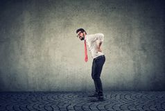 Young businessman with backache on gray background royalty free stock photos