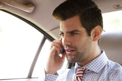 Young businessman in the backseat of car Stock Photos